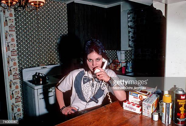 Guitarist Joan Jett of the rock band 'The Runaways' poses for a portrait wearing a tuxedo tshirt on the phone in her family kitchen in Canoga Park...