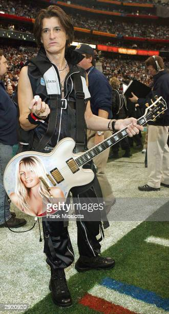 Guitarist Joe Perry of Aerosmith poses before performing at the pregame show prior to the start of Super Bowl XXXVIII between the New England...