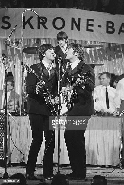 Guitarist John Lennon, bass guitarist Paul McCartney and drummer Ringo Starr of The Beatles performing at their first concert on their tour of...