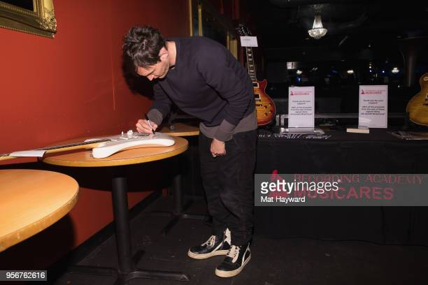 Guitarist Josh Klinghoffer of Red Hot Chili Peppers autographs a guitar after rehearsal for the Musicares Concert for Recovery at the Showbox on May...