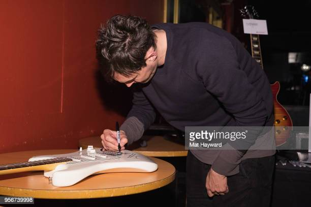 Guitarist Josh Klinghoffer of the Red Hot Chili Peppers signs an autograph after rehearsal for the Musicares Concert for Recovery at the Showbox on...