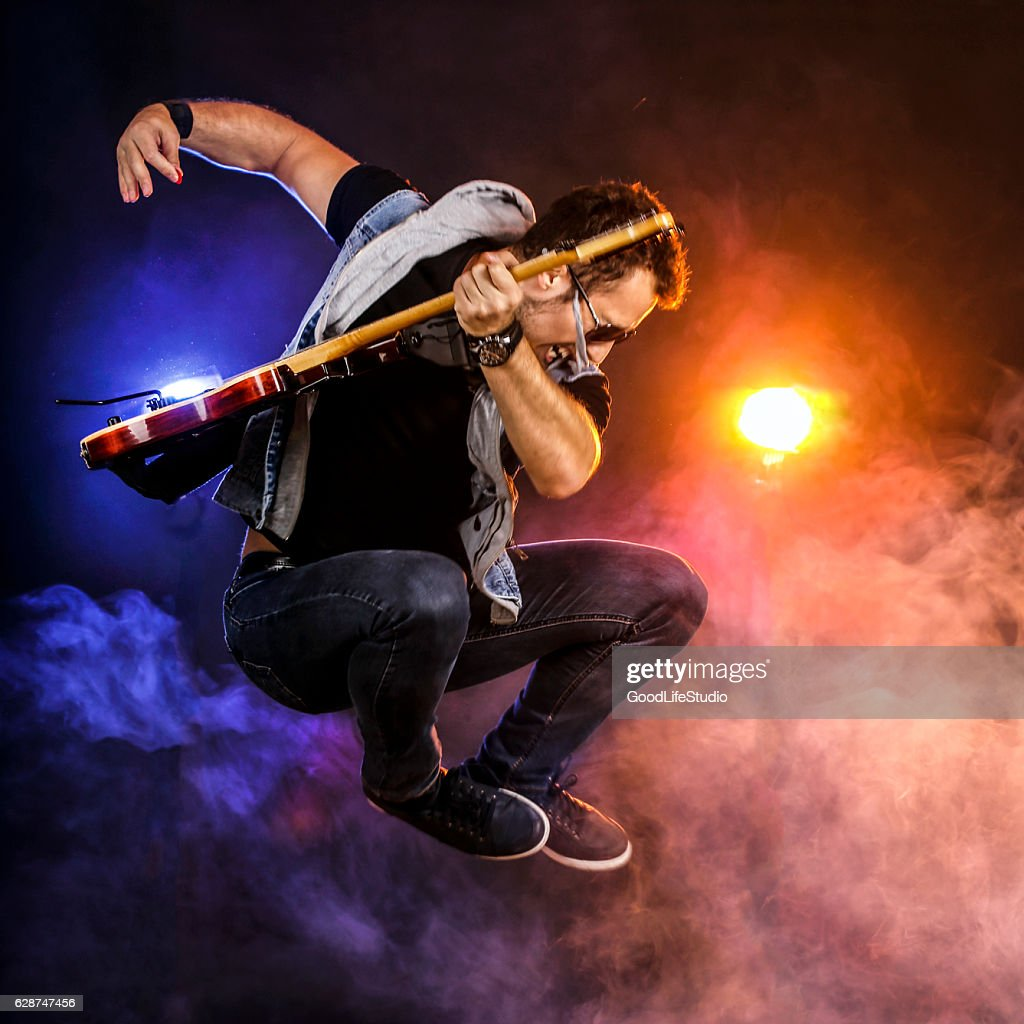 Guitarist jumping on stage : Stock Photo
