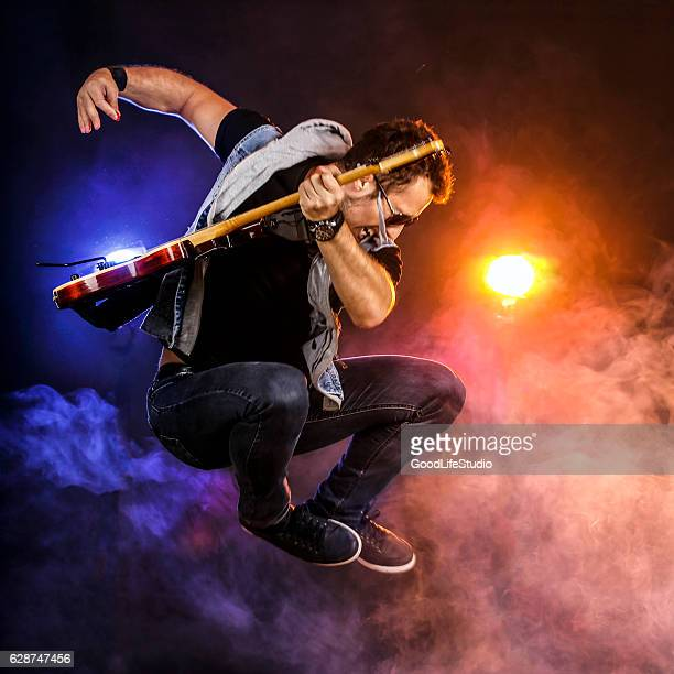 guitarist jumping on stage - rock stock pictures, royalty-free photos & images