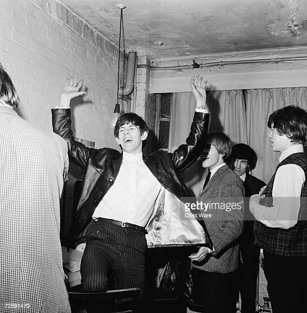 Guitarist Keith Richards laughing with Mick Jagger Brian Jones and Bill Wyman backstage during an early Rolling Stones tour December 1963