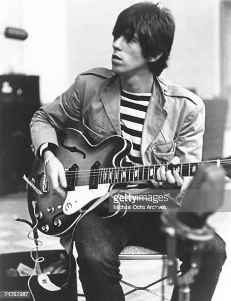 Guitarist Keith Richards of the Rolling Stones sits on a chair in a recording studio and strums his Epiphone guitar in 1966