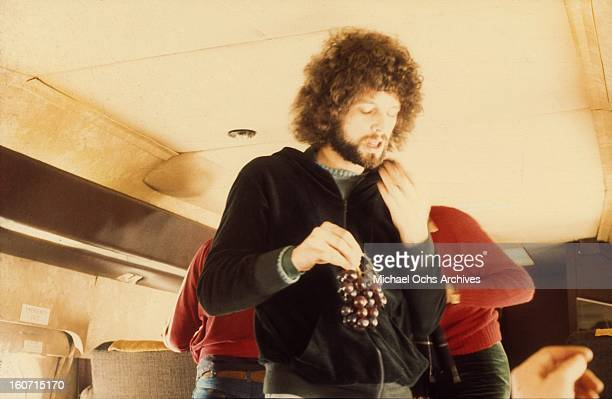 Guitarist Lindsey Buckingham of the Rock group 'Fleetwood Mac' eats grapes on board their private jet in circa 1975.