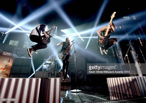 Guitarist Michael Clifford singer Luke Hemmings and guitarist Calum Hood of 5 Seconds of Summer rehearse onstage during the 2014 Billboard Music...