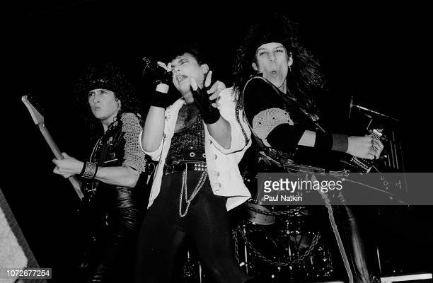 Guitarist Michael Wilton, left, singer Geoff Tate, center, and guitarist Chris Degarmo of Queensryche perform at the Milwaukee Arena in Milwaukee,...