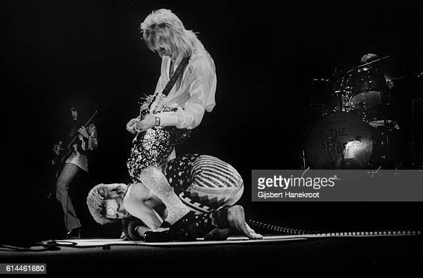 Guitarist Mick Ronson stands astride David Bowie as they perform on stage on the Ziggy Stardust tour Earls Court Arena London 12th May 1973