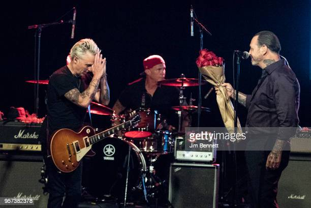 Guitarist Mike McCready receives roses from singer and guitarist Mike Ness while drummer Chad Smith looks on during the MusiCares Concert for...