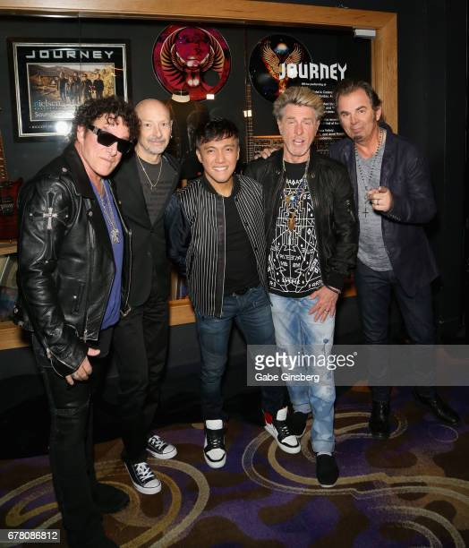 Guitarist Neal Schon drummer Steve Smith singer Arnel Pineda bassist Ross Valory and keyboardist Jonathan Cain of Journey attend a memorabilia case...
