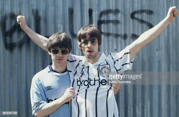 Guitarist Noel Gallagher and his brother singer Liam Gallagher of British rock group Oasis posing in Manchester City football shirts 9th May 1994 The...
