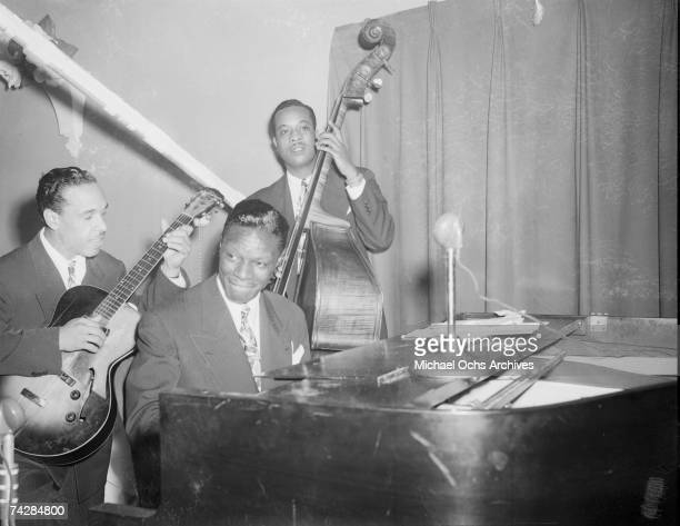 Guitarist Oscar Moore pianist Nat 'King' Cole and bassist Johnny Miller of the 'Nat 'King' Cole Trio' record in Capitol Records studios on December...
