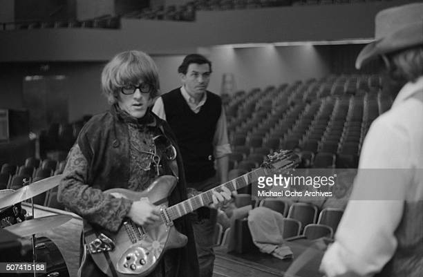 Guitarist Paul Kantner of the rock group Jefferson Airplane rehearses for a concert as promoter Bill Graham looks on at Hunter College in New York...