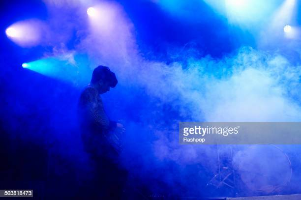 guitarist performing on stage at music concert - tegenlicht stockfoto's en -beelden