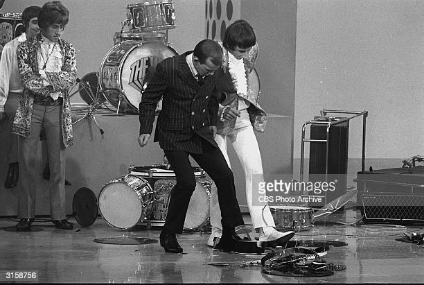 Guitarist Pete Townshend and host Tom Smothers stomp on the shards of Smothers' acoustic guitar as singer Roger Daltrey and drummer Keith Moon look...