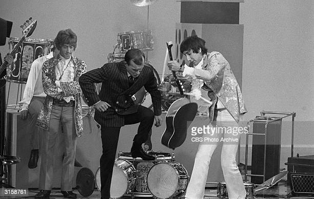 Guitarist Pete Townshend helps host Tom Smothers destroy his acoustic guitar as singer Roger Daltrey looks on following British rock group The Who's...