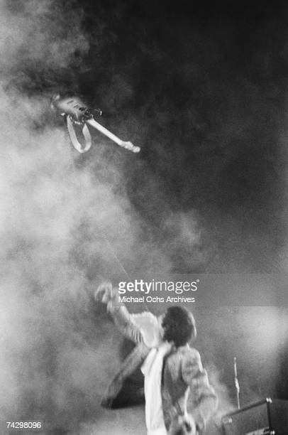 Guitarist Pete Townshend of the rock and roll band 'The Who' tosses his electric guitar in midair as he performs onstage at Atwood Stadium on August...