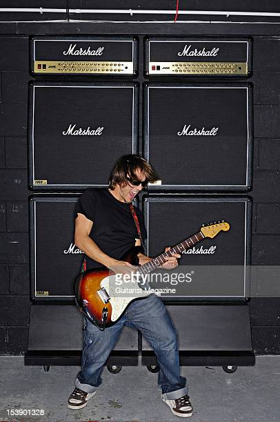 A guitarist playing a Fender Stratocaster electric guitar in front of a stack of Marshall electric guitar amplifiers during a studio shoot for...
