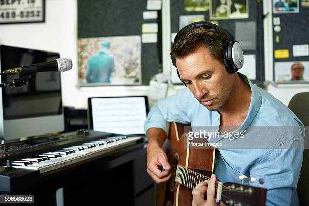 guitarist playing guitar at home - string instrument stock photos and pictures