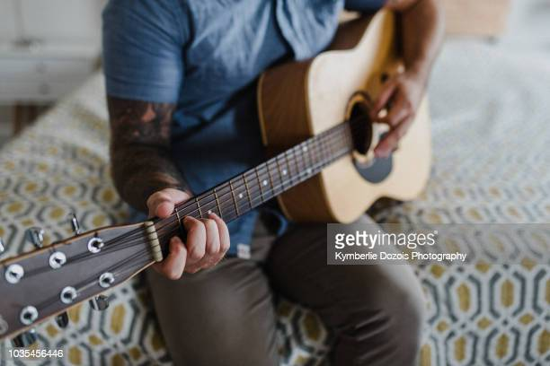 Guitarist playing music on bed