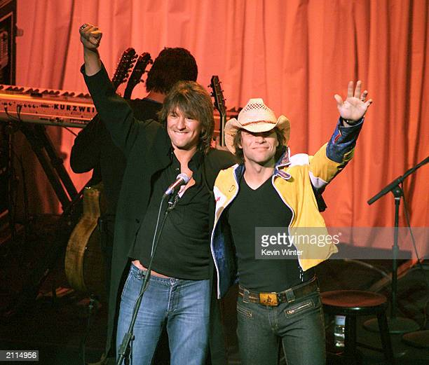Guitarist Richie Sambora and singer Jon Bon Jovi of the group Bon Jovi wave on stage during 'The Concert20 Years With AIDS' at the Universal...