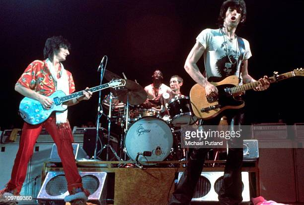Guitarist Ronnie Wood percussionist Ollie Brown drummer Charlie Watts and guitarist Keith Richards of the Rolling Stones performing on stage during...