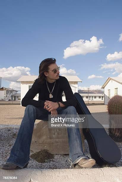 Guitarist sitting at roadside