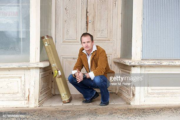 Guitarist Squatting in Front of Old Building