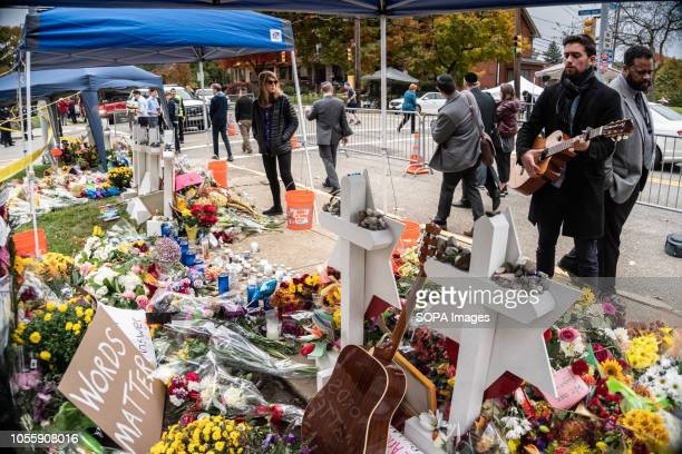 A guitarist stood passionately singing for hours Outside the Tree of Life many come to pay their respects whether it be rain or shine Musicians from...