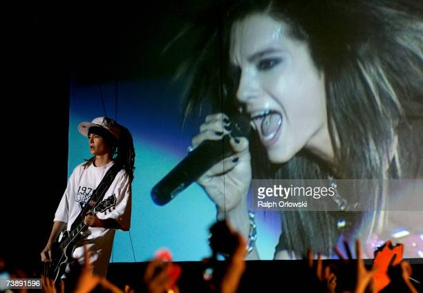 Guitarist Tom Kaulitz of German pop group Tokio Hotel performs on stage in front of a huge video screen showing his brother Bill during a concert at...