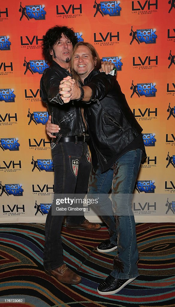 Guitarist Tracii Guns (L) and singer/guitarist Andrew Freeman joke around at the 'Night of the Champion' event to honor former boxer Leon Spinks hosted by the cast members of 'Raiding the Rock Vault' at The Las Vegas Hotel & Casino on August 17, 2013 in Las Vegas, Nevada.