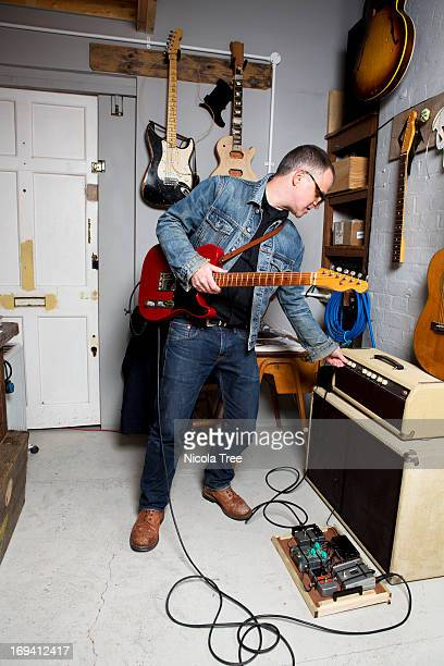 a guitarist turning on amplifier - guitar stock pictures, royalty-free photos & images