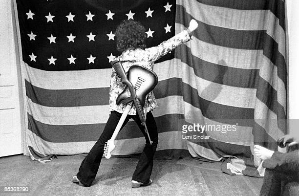 Guitarist Wayne Kramer of The group MC5 poses in front of an American flag in 1969 in East Lansing Michigan