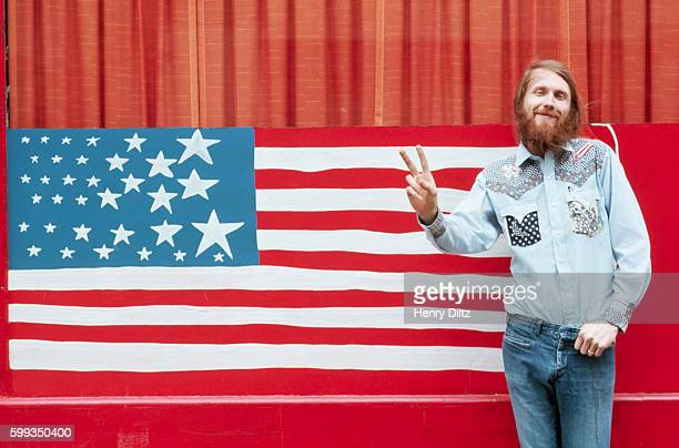Guitarist William Truckaway gives the two finger '' symbol before a handpainted American flag design during the early 1970s at the time of the...