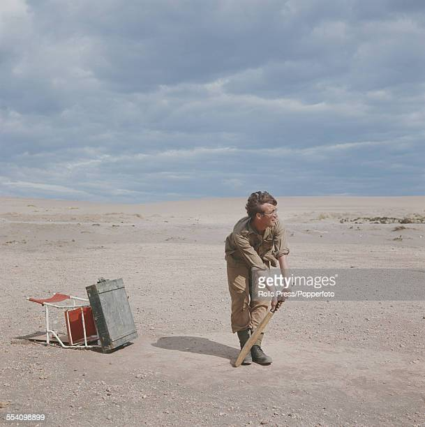 Guitarist with The Beatles John Lennon pictured dressed in character as Muskateer Gripweed plays an impromptu game of cricket on location in Almeria...