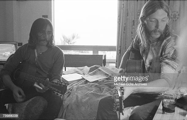 Guitarists Duane Allman and Dickey Betts use a steel slide on an acoustic guitars in a hotel room before the Allman Brothers' performance at the...