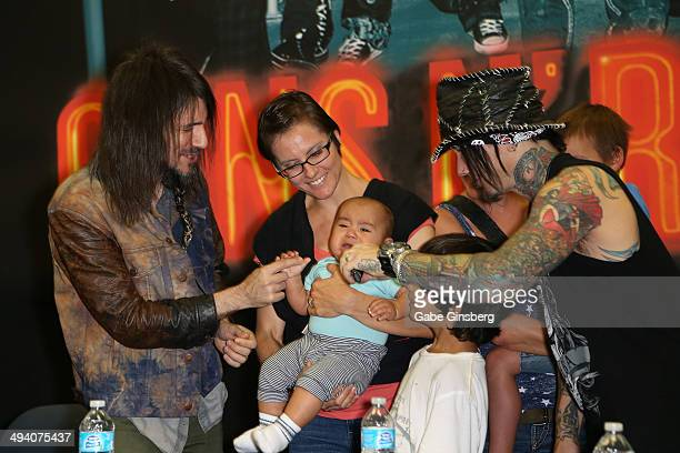 Guitarists Ron Bumblefoot Thal and Dj Ashba of Guns N' Roses try to entertain a crying baby at a meetandgreet at Nellis Air Force Base on May 27 2014...