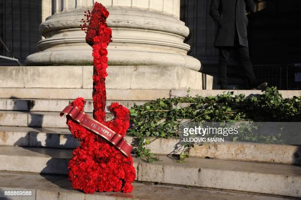A guitarshaped floral wreath featuring the name of one of Paris' iconic music hall venues 'L'Olympia' stands outside the La Madeleine Church prior to...