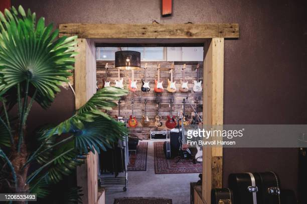 guitarshop with elctrical guitars hanging on the wall - finn bjurvoll stock pictures, royalty-free photos & images