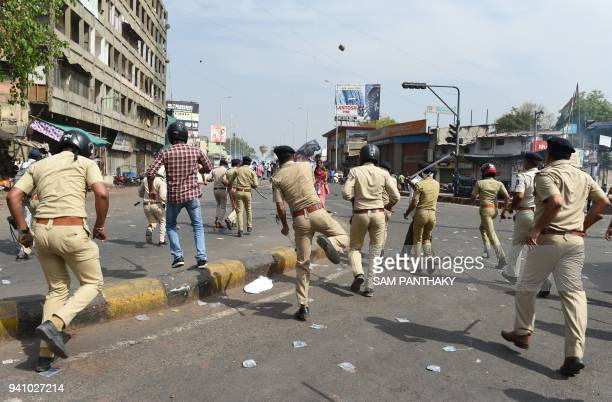 A Gujarat Police official during clashes with members of the Scheduled Castes at a protest against a Supreme Court order that allegedly diluted the...