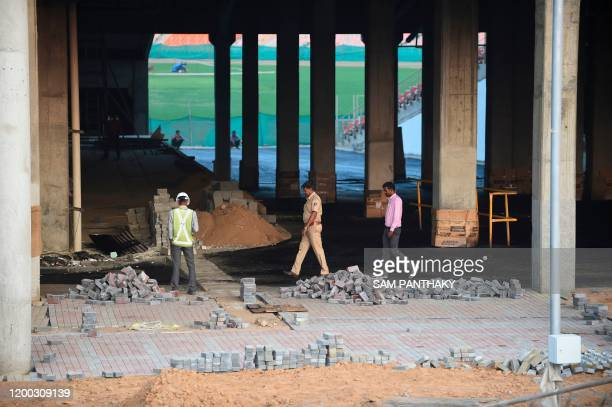 A Gujarat police official walks inside an under construction area of the Motera stadium the world's largest cricket stadium on the outskirts of...