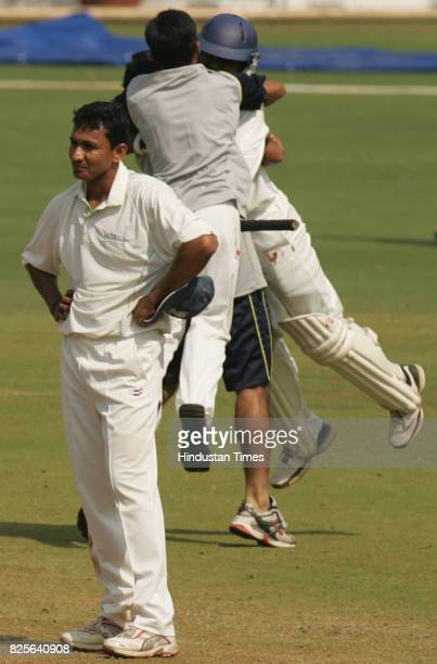 Gujarat team members rush towards notout batsman Jay Desai who guided Gujarat to the victory against Railways as Rlys bowler Sanjay Bangar who took 6...