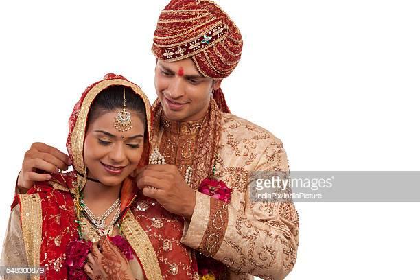 gujarati groom tying a mangal sutra around brides neck - mangala sutra fotografías e imágenes de stock