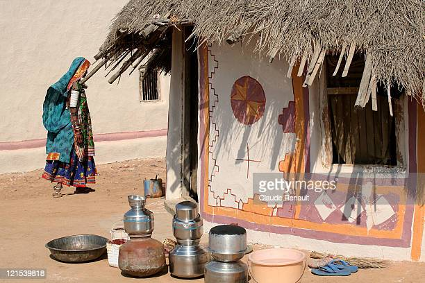 gujarati woman walking by  hut in village - gujarat stock pictures, royalty-free photos & images