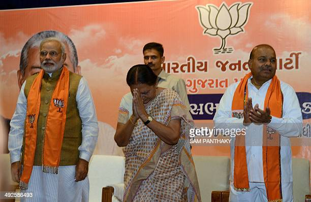 Gujarat's first woman chief minister Anandiben Patel greets the audience as Indian prime ministerelect Narendra Modi and BJP central observer Thawar...