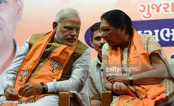 Gujarat's first woman chief minister Anandiben Patel interacts with Indian prime ministerelect Narendra Modi at the Town Hall in Gandhinagar some 30...
