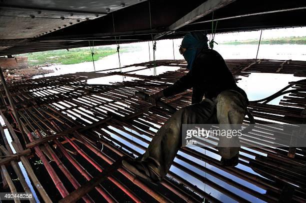 Gulab Kumar doing sandblasting on iron bridge standing on handmade temporary platform in the middle of the river Yamuna and Iron Bridge on June 22...