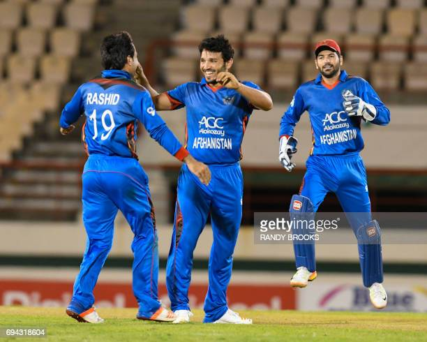 Gulbadin Naib Rashid Khan Arman and Afsar Khan Zazai of Afghanistan celebrate the dismissal of Evin Lewis of West Indies during the 1st ODI match...