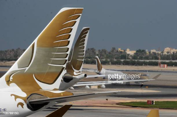 Gulf Air logos are seen on the tailfins of the company's Airbus A330 airliners left while a Gulf Air Embraer 170 aircraft right taxis on the tarmac...